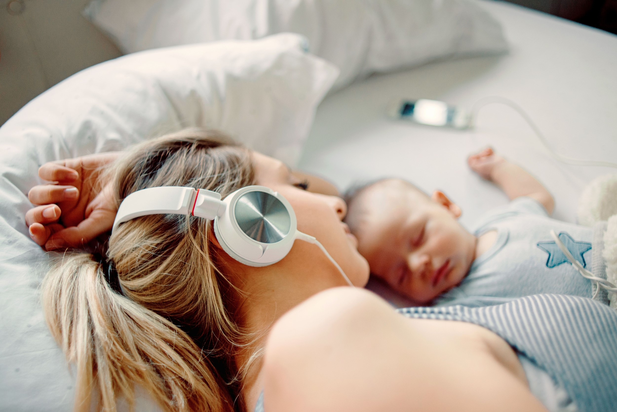 Woman lying next to hear newborn, listening to a postpartum affirmations MP3